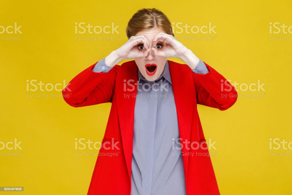 Red head woman in red suit looking in binoculars far far away. stock photo