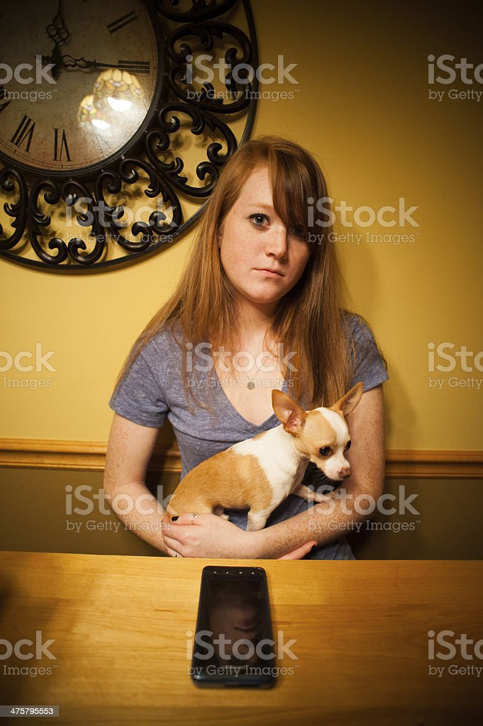 Red headed girl with chihuahua and cellphone stock photo