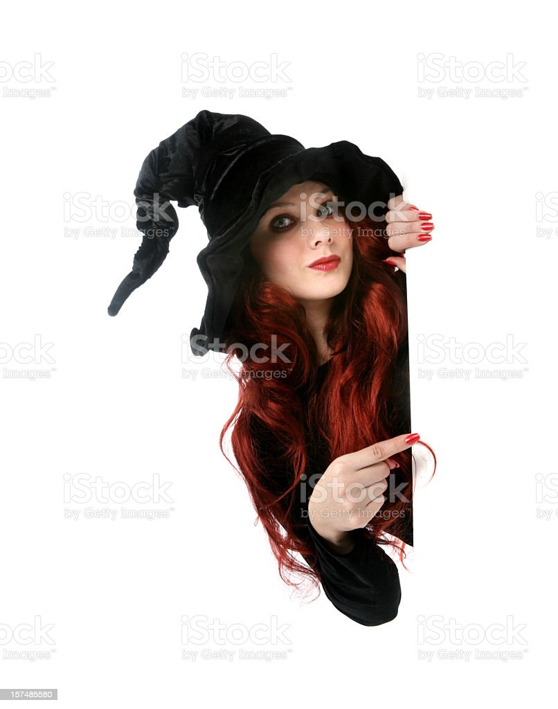 A red headed witch pointing to something in the distance stock photo