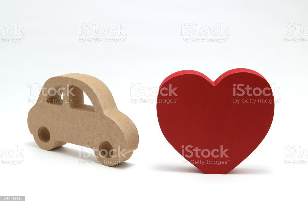 Red heart and a toy miniature wooden car on white background. Safe driving concept. stock photo