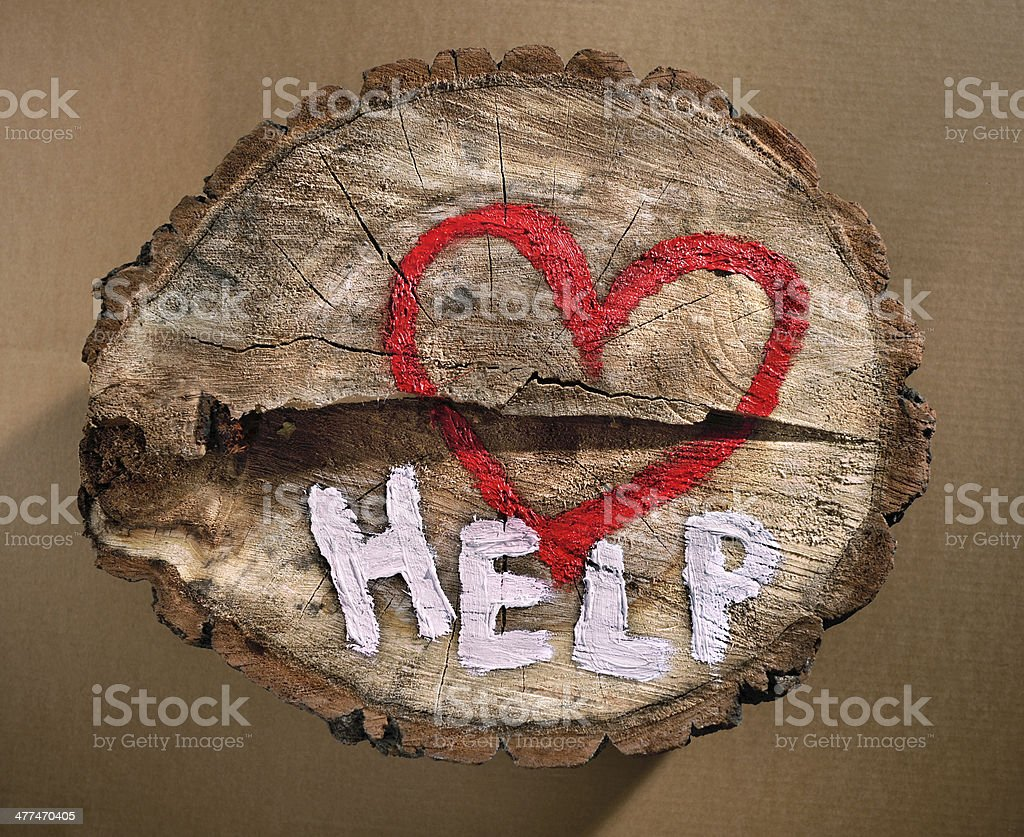 Red heart and the word 'help' painted on tree trunk. stock photo