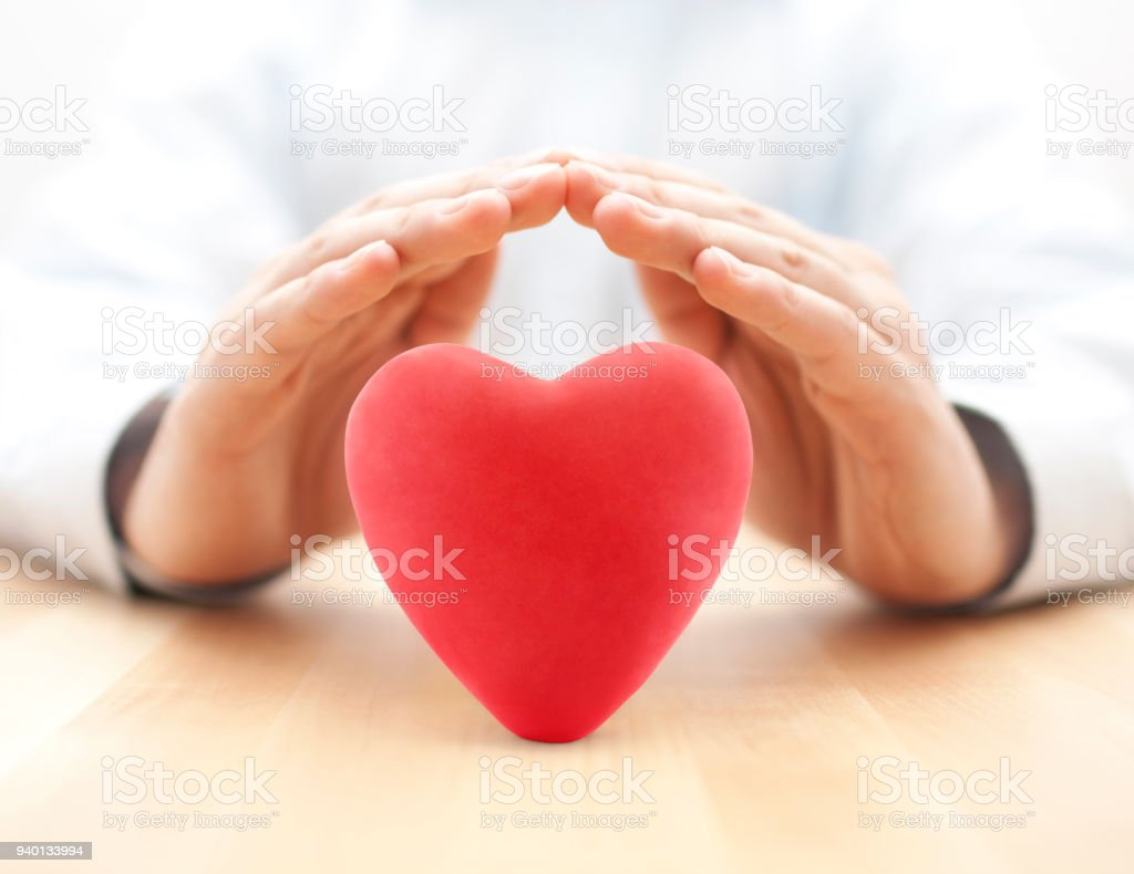 Red heart covered by hands. Health insurance or love concept stock photo