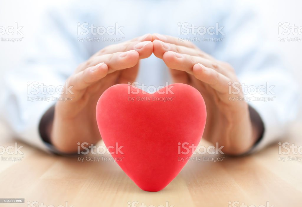 Red heart covered by hands stock photo