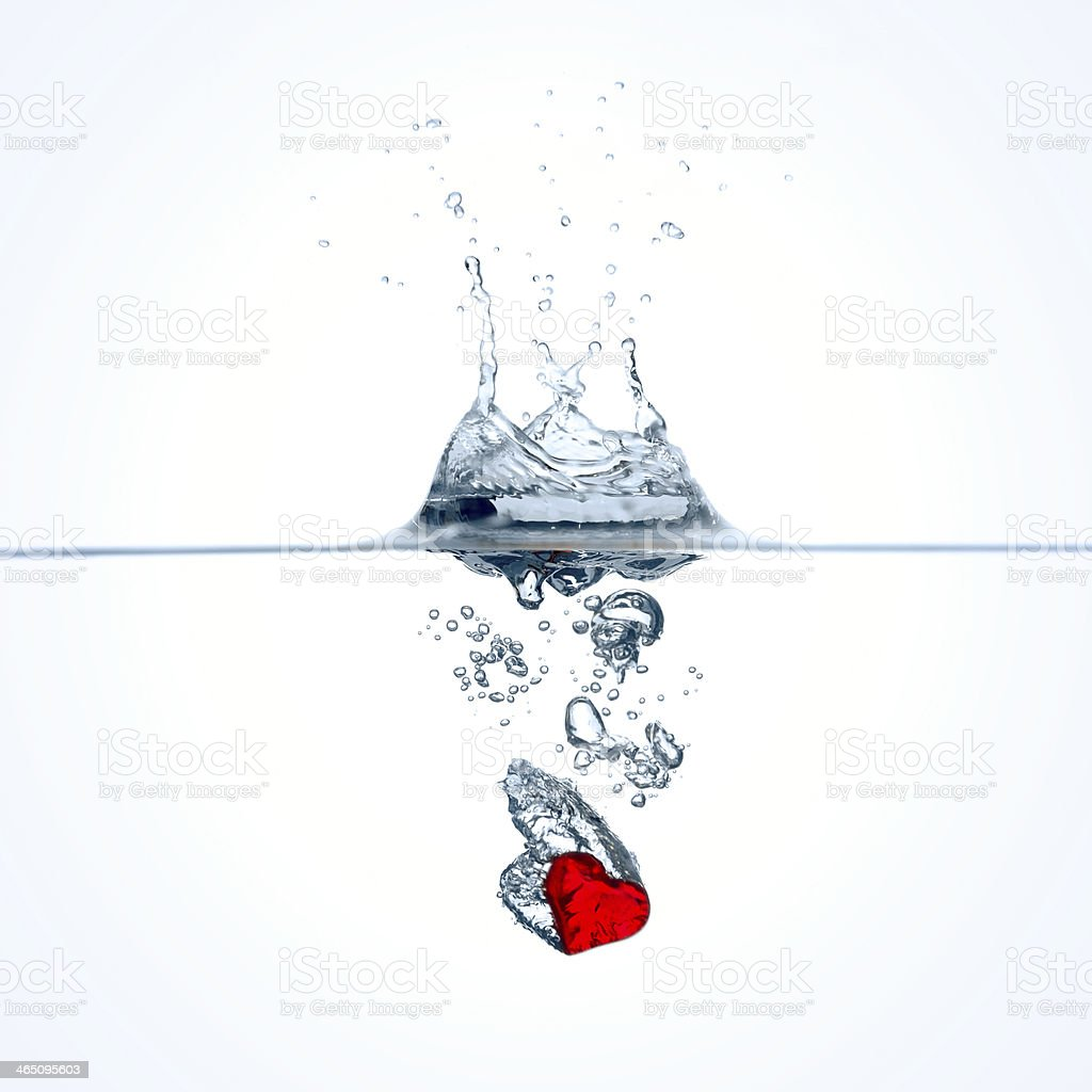 Red heart falling into water stock photo