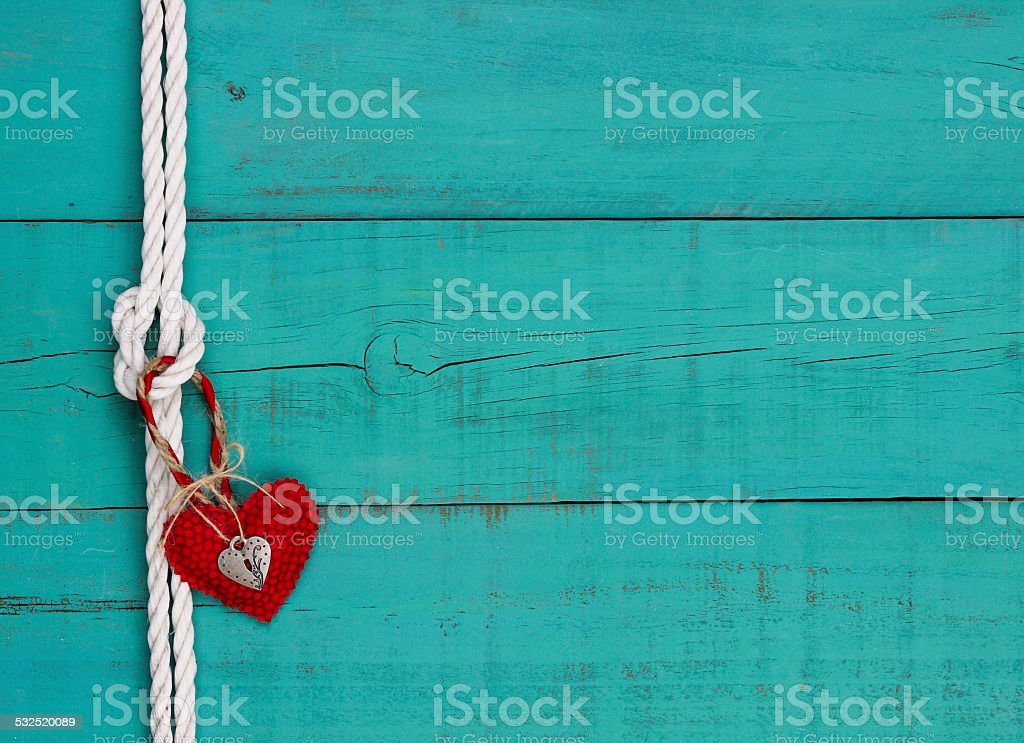 Red heart hanging on rope knot with blue wood background stock photo
