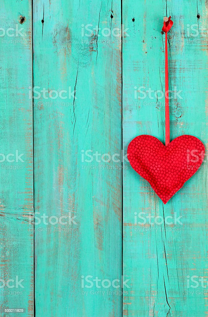 Red heart hanging on teal blue wood background stock photo