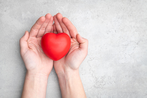 istock Red heart holding in female hands 1131121727