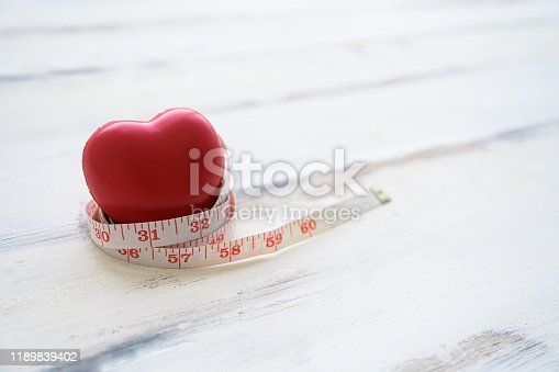 917079152istockphoto Red heart icon and measuring tape on wooden table. Concept healthcare medical, Insurance for your health 1189839402