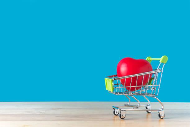 coração vermelho em um carrinho de compras em um de madeira com fundo azul. para o conceito de dia dos namorados. com espaço de cópia para sua mensagem de texto - dia do cliente - fotografias e filmes do acervo