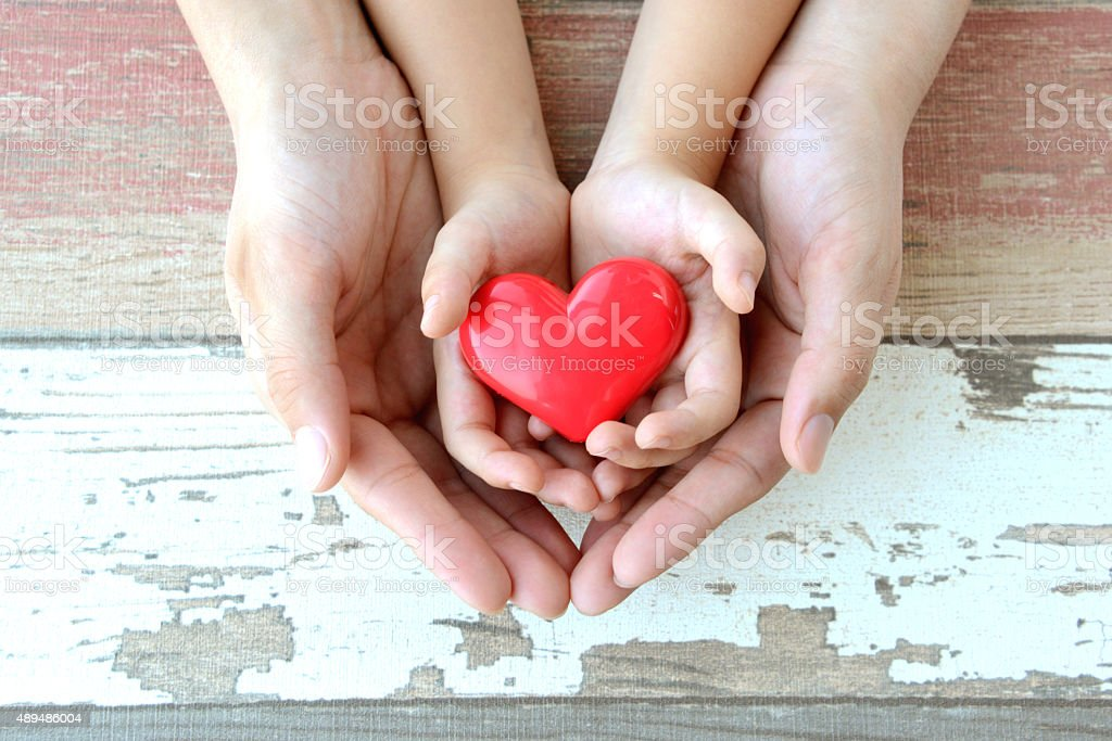 Red heart in child and mother's hands stock photo