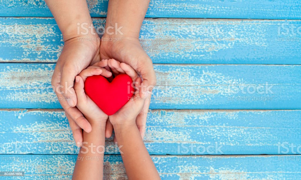 Red heart in child kid and mother hands on old blue wooden table stock photo