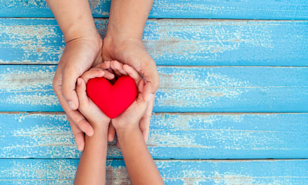 red heart in child kid and mother hands on old blue wooden table - mother stock photos and pictures