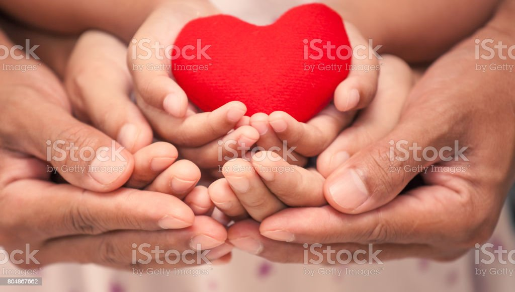 Red heart in child kid  mother and father hands in vintage color tone - foto stock