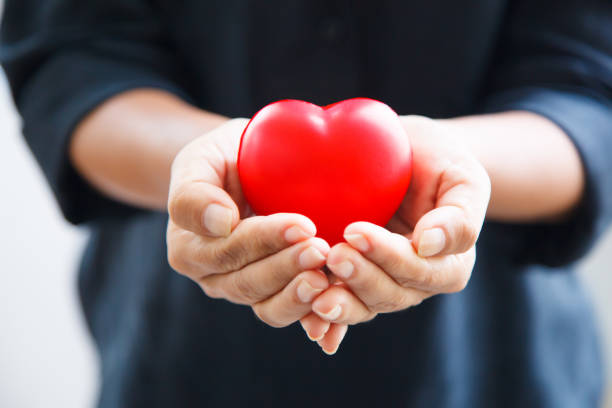 red heart in female's both hands in black suit background, represents helping hands in hard time, caring, love, sympathy, condolence, patient assistance, life moment, psychological support concept - coração fraco imagens e fotografias de stock