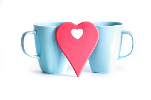 Red heart in front of two blue cups on white