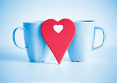 Red heart in front of two blue cups