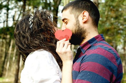 518335358 istock photo Red heart in hands of beautiful young couple 971636500