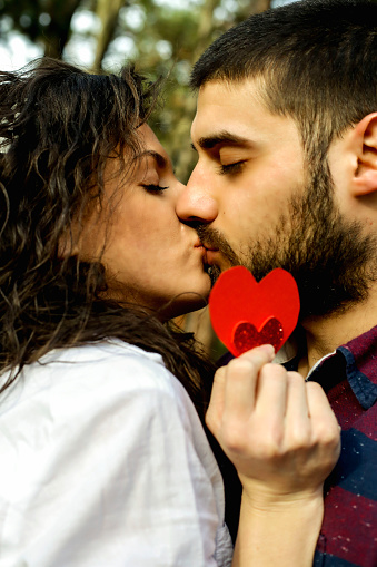 518335358 istock photo Red heart in hands of beautiful young couple 971636668