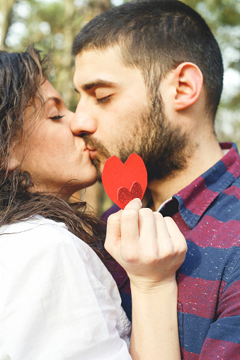 518335358 istock photo Red heart in hands of beautiful young couple 971636812