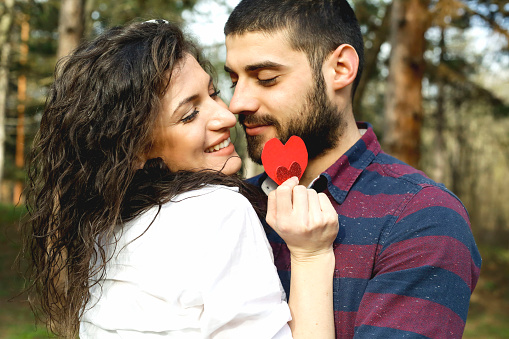 518335358 istock photo Red heart in hands of beautiful young couple 971636902