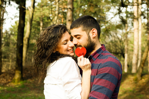 518335358 istock photo Red heart in hands of beautiful young couple 971637008