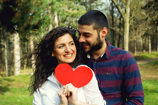 518335358 istock photo Red heart in hands of beautiful young couple 971637126