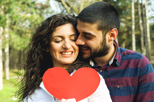 518335358 istock photo Red heart in hands of beautiful young couple 971637318