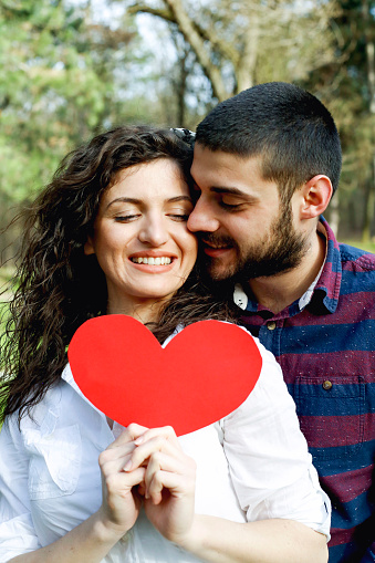 518335358 istock photo Red heart in hands of beautiful young couple 971639262