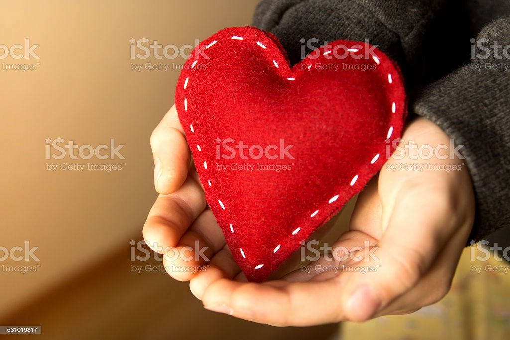 Red heart in hands stock photo