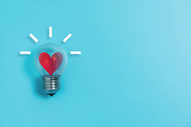Red heart in light bulb on blue background with copy space. stock photo