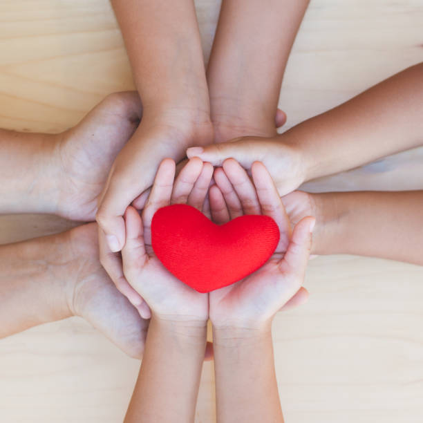 Red heart in parent and children holding hands together on wooden background - foto stock
