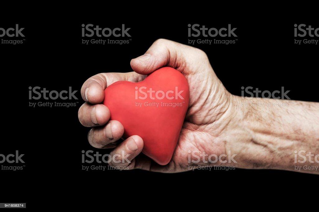 Red heart in senior hand over black background stock photo