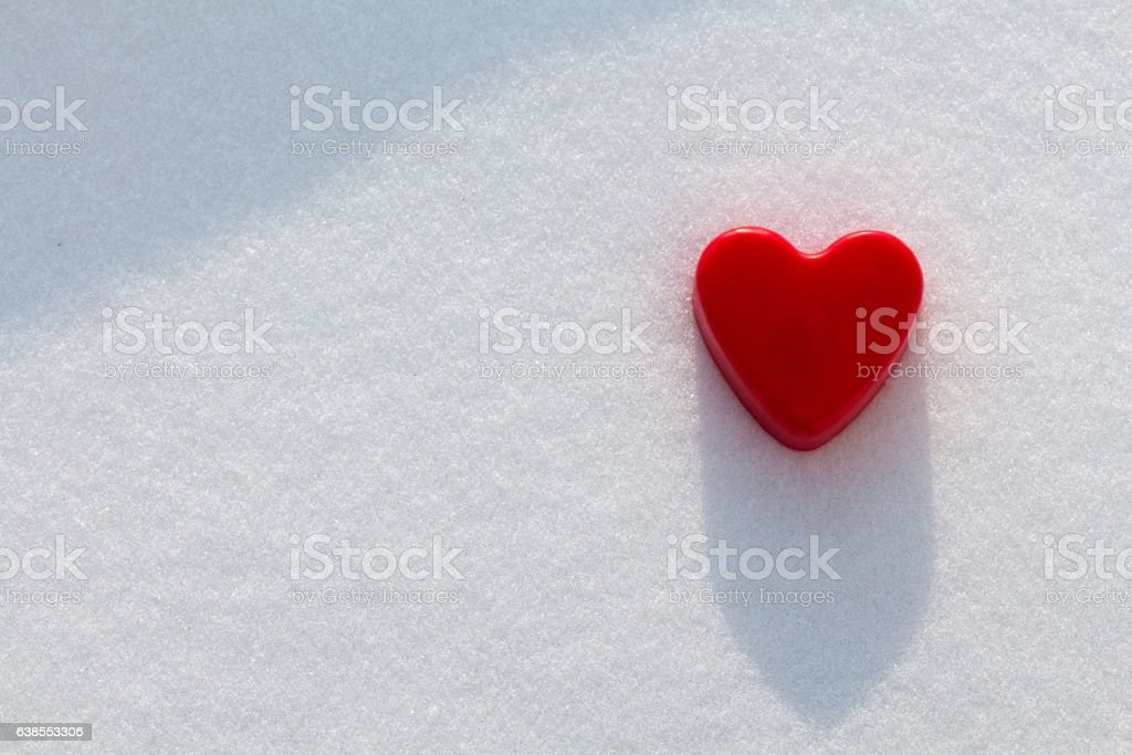 Red heart in the snow with sunshine stock photo