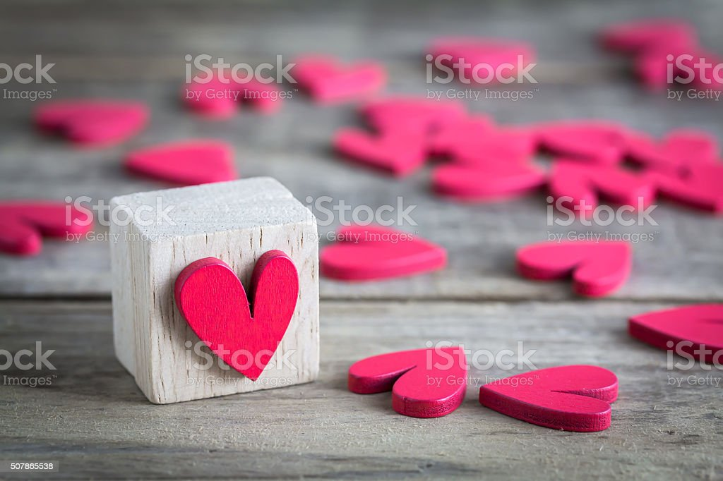 Red Heart In Wooden Cube Stands On Amongst The Hearts Stock Photo