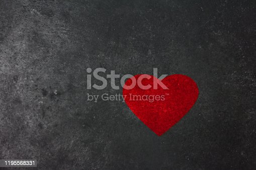 a big red heart on a rough dark wall with soot from the fire. war and peace concept.
