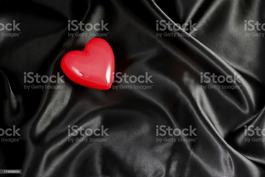 Red heart on black satin background royalty-free stock photo