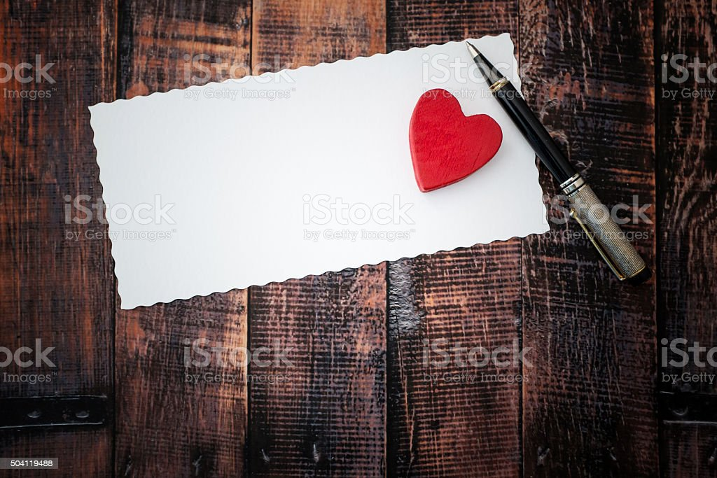 Red heart on white paper sheet, top view stock photo