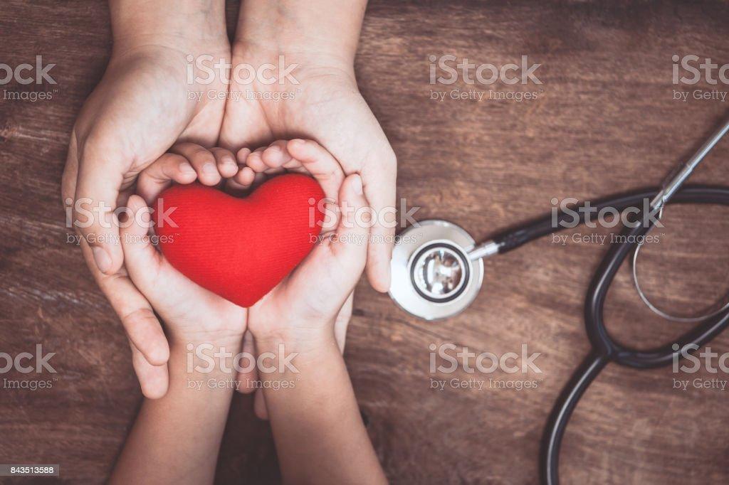 Coração vermelho nas mãos de mulheres e crianças e com o estetoscópio do médico em fundo de madeira foto de stock royalty-free