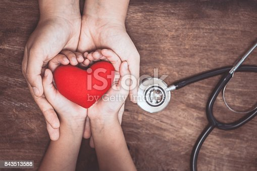 istock Red heart on woman and child hands and with doctor's stethoscope on wooden background 843513588