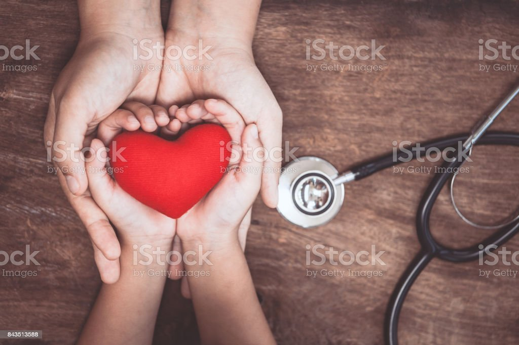 Red heart on woman and child hands and with doctor's stethoscope on wooden background stock photo