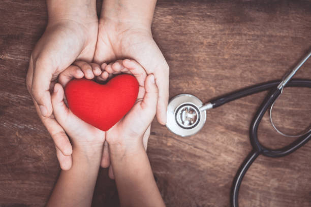 red heart on woman and child hands and with doctor's stethoscope on wooden background - health and beauty stock photos and pictures