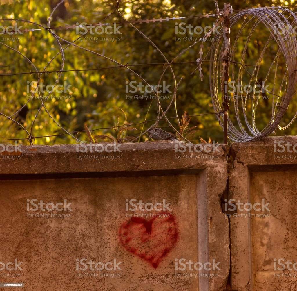 red heart painted on a concrete wall, against the backdrop of barbed wire, the concept of prison, salvation, Refugee, Silent,  lonely, broken love, relationship, lonely, obstacle,  platonic one sided stock photo