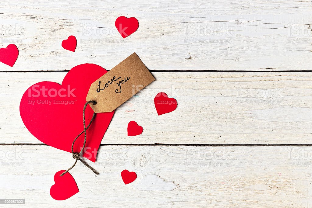 Red heart paper cut on white wooden background. stock photo