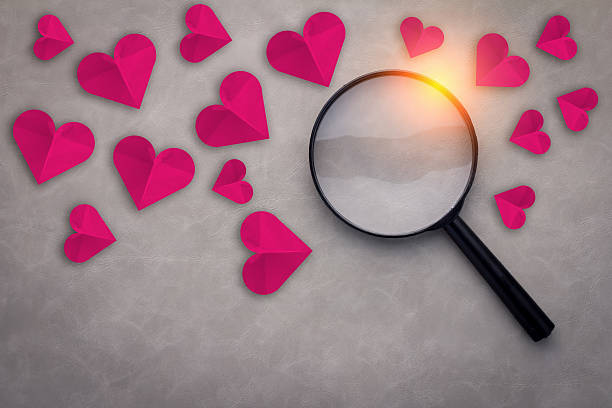 red heart paper with magnifying glass - a procura de amor - fotografias e filmes do acervo