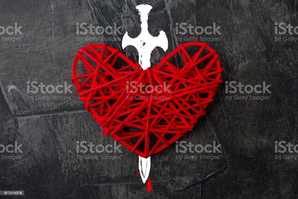 Red heart pierced with a sword. The theme of broken love stock photo