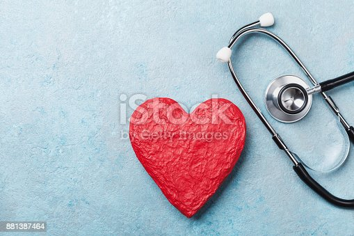 istock Red heart shape and medical stethoscope on blue background top view. Health care, medicare and cardiology. 881387464