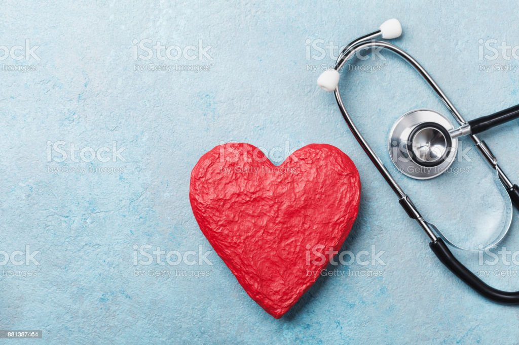 Red heart shape and medical stethoscope on blue background top view. Health care, medicare and cardiology. stock photo