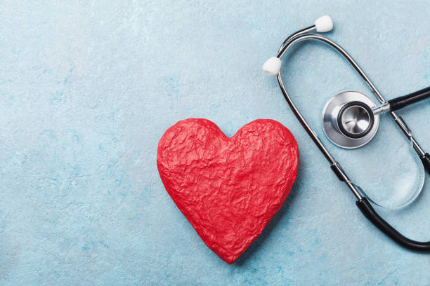 red heart shape and medical stethoscope on blue background top view. health care, medicare and cardiology. - screening stock photos and pictures