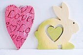 Red heart shape and wooden bunny on white background