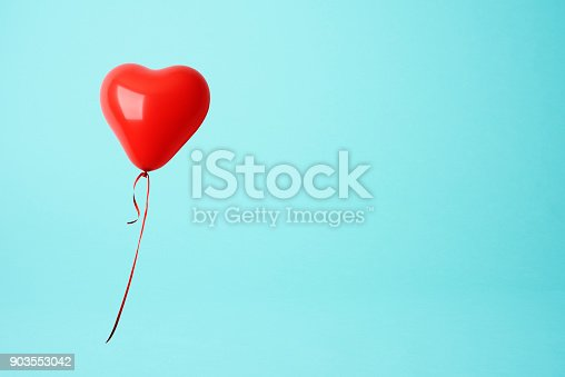 Red heart shape balloon against blue background with copy space.